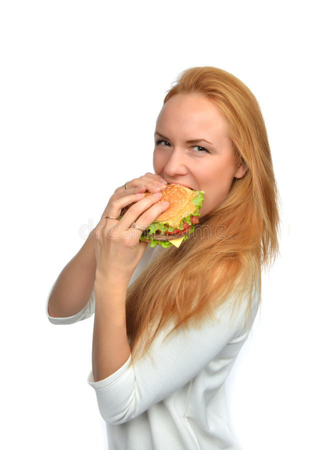 Fast food concept. Woman eating tasty unhealthy burger sandwich. In hands hungry getting ready to eat isolated on a white background royalty free stock photos