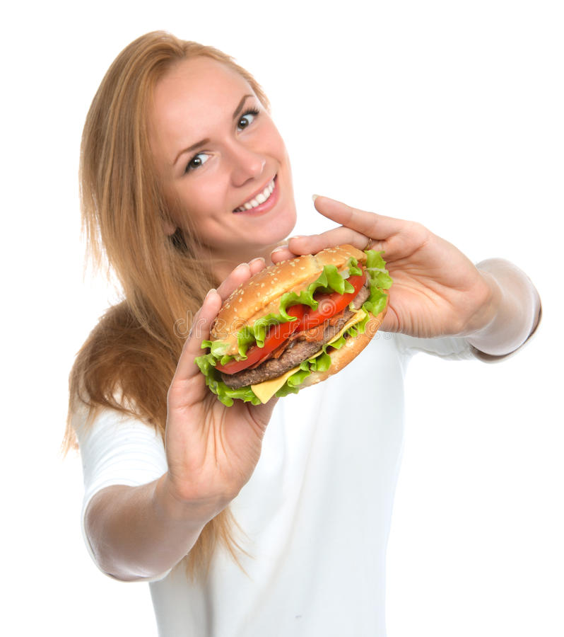 Fast food concept. Woman show tasty unhealthy burger sandwich. In hands hungry getting ready to eat isolated on a white background royalty free stock photo