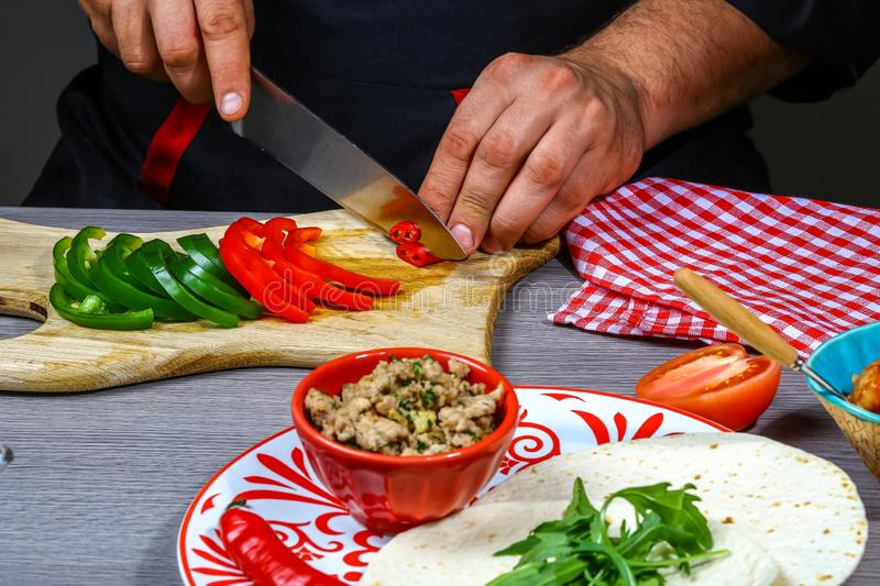 Fast food cooking. Hands preparing tortilla wrap with cuts meat and vegetable salad, mexican burito royalty free stock image