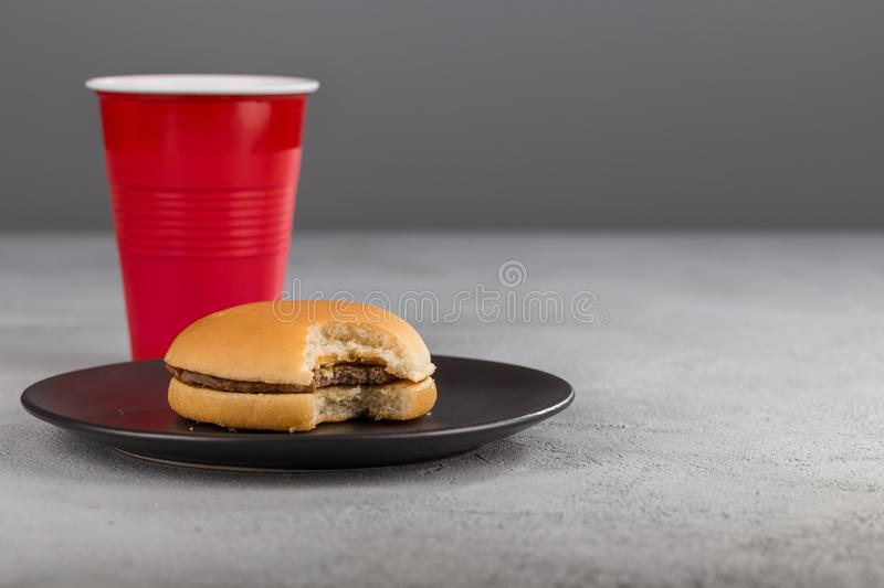 Fast food with delicious bitten hamburger on the background of a red Cup with a drink. stock images