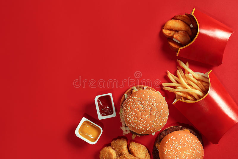 Fast food dish top view. Meat burger, potato chips and nuggets on red background. Takeaway composition. Wrapped French fries, hamburger, mayonnaise and ketchup royalty free stock images