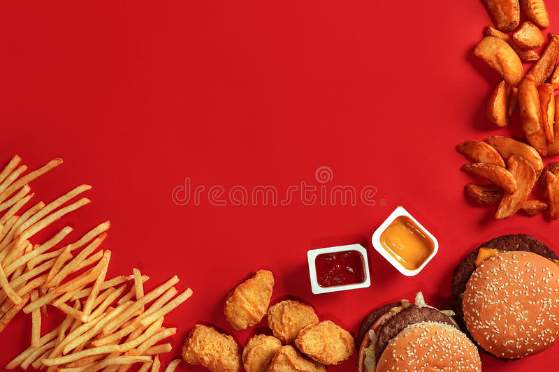 Fast food dish top view. Meat burger, potato chips and nuggets on red background. Takeaway composition. Wrapped French fries, hamburger, mayonnaise and ketchup stock image
