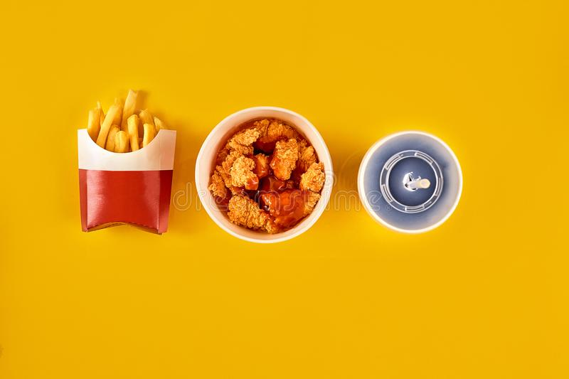 Fast food dish on yellow background. Fast food set fried chicken and french fries. Take away fast food. royalty free stock images