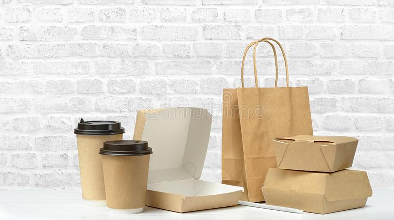 Fast food and drink packaging. Fast food packaging set. Empty open food box, paper coffee cups, brown paper bag on the table on white brick wall background stock images
