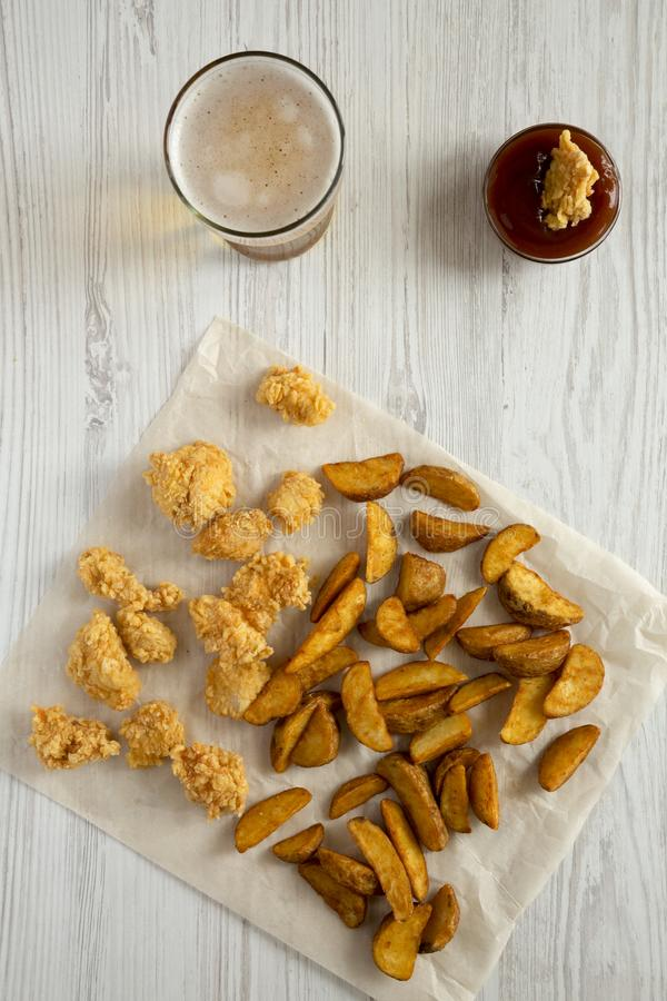 Fast food: fried potato wedges, chicken bites, beer and bbq sauce on a white wooden table, top view. Overhead, from above stock photo