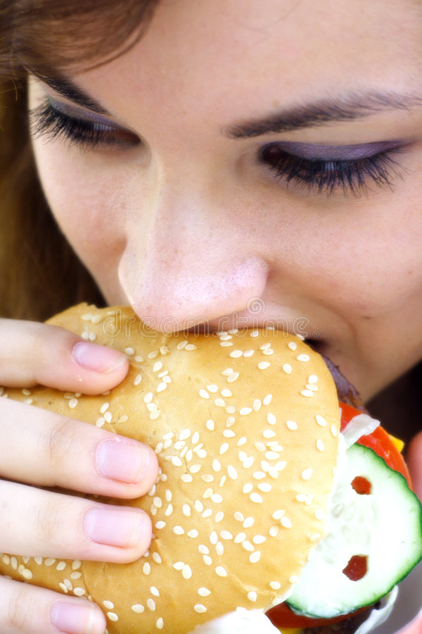 Fast food girl. Pretty girl eating a fast food hamburger royalty free stock image