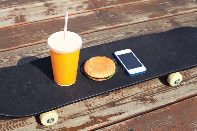 Fast food i niezdrowy łasowania pojęcie - sok filiżanka, hamburger, smartphone na deskorolka fotografia royalty free