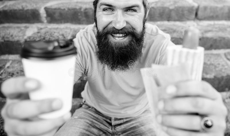 Fast food for lunch common idea. Hipster enjoy hot dog and drink paper cup beverage. Man bearded enjoy street food. Stairs background. Hipster eat hot dog and stock photo