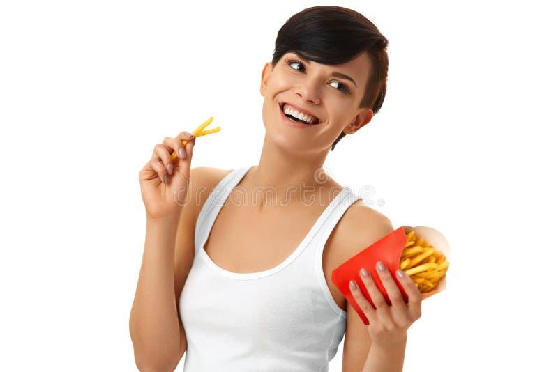 Fast food Menina que come batatas fritas Fundo branco Alimento concentrado fotografia de stock royalty free