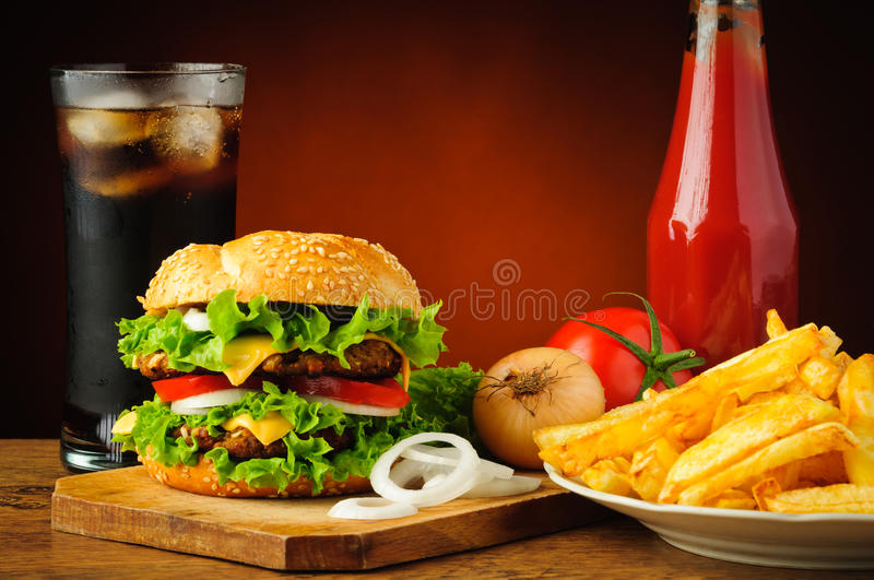 Fast food menu. With big tasty hamburger, vegetables, french fries, tomato ketchup and cola drink stock photos