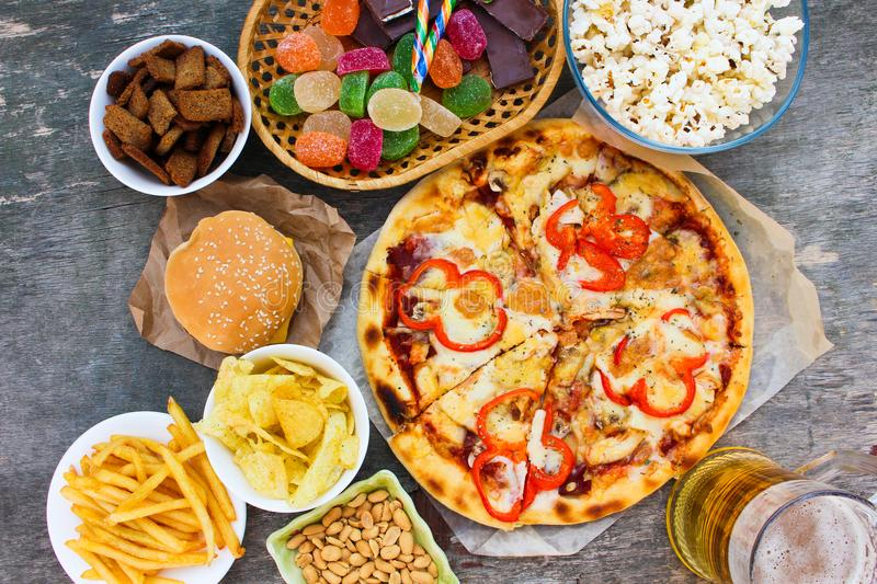 Fast food on old wooden background. Concept of junk eating. royalty free stock images