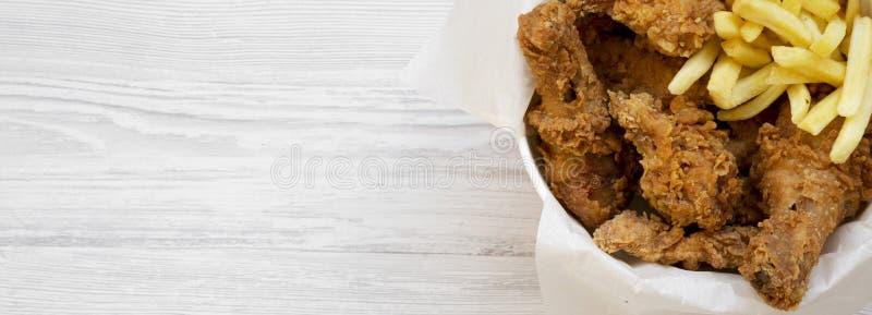 Fast food: pieczonych kurczaków drumsticks, korzenni skrzydła, francuzów dłoniaki i kurczaków paski w papierowym pudełku nad biał zdjęcie stock