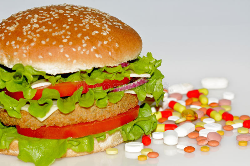 Fast food and pills. On white background stock photo