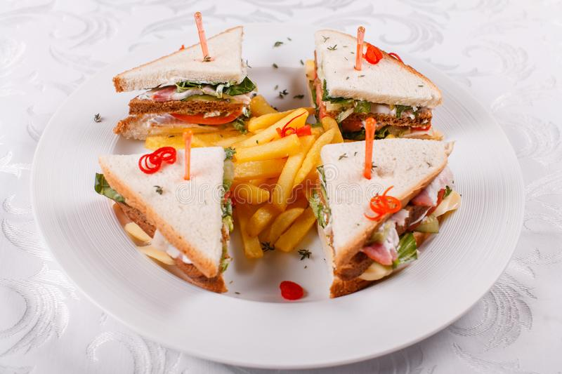 Fast food restaurant menu. Club sandwich with cheese, pIckled cucmber, tomato and smoked meat. Garnished with golden. French fries potatoes royalty free stock photo