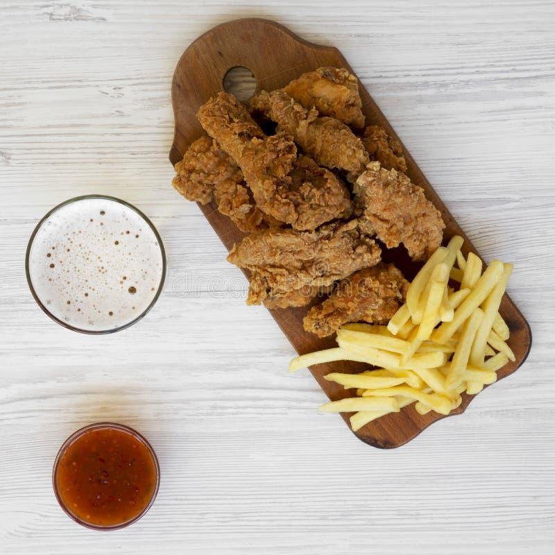 Fast food saboroso: pilões de frango frito, asas picantes, batatas fritas e dedos da galinha com molho e vidro ácido-doces do fri foto de stock royalty free
