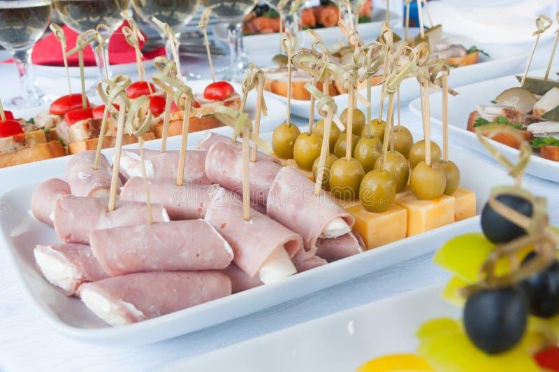 Fast food, szybkie żarcie, catering i niezdrowy łasowania pojęcie, - zamyka up canape kanapki na porci lub hamburgery obrazy stock