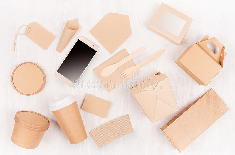 Fast food template for branding identity - blank kraft paper bag, coffee cup, label, card, box for noodles, screen phone on wood. royalty free stock image