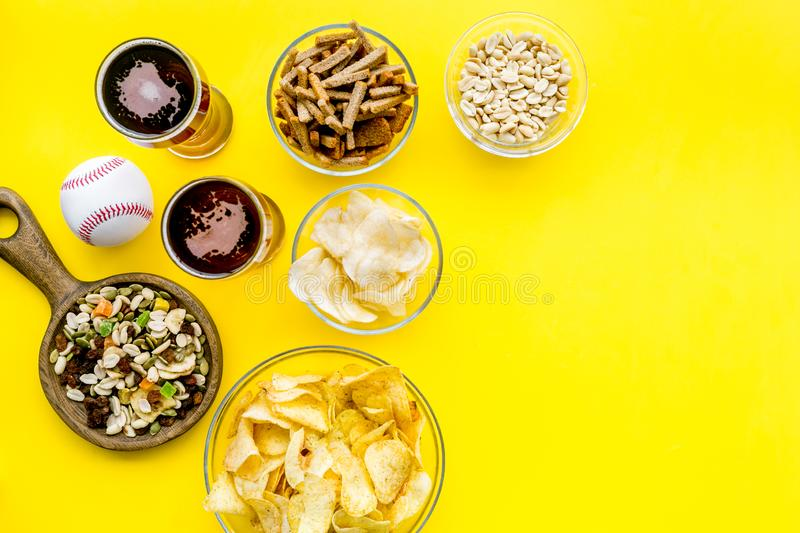 Fast food for TV watching. Snacks on desk. Chips, nuts, rusks and beer on yellow background top view copy space royalty free stock image