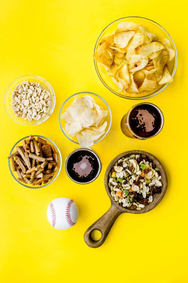 Fast food for TV watching. Snacks on desk. Chips, nuts, rusks and beer on yellow background top view copy space royalty free stock photography