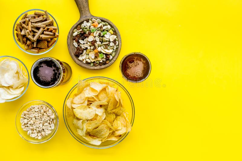Fast food for TV watching. Snacks on desk. Chips, nuts, rusks and beer on yellow background top view space for text royalty free stock photos