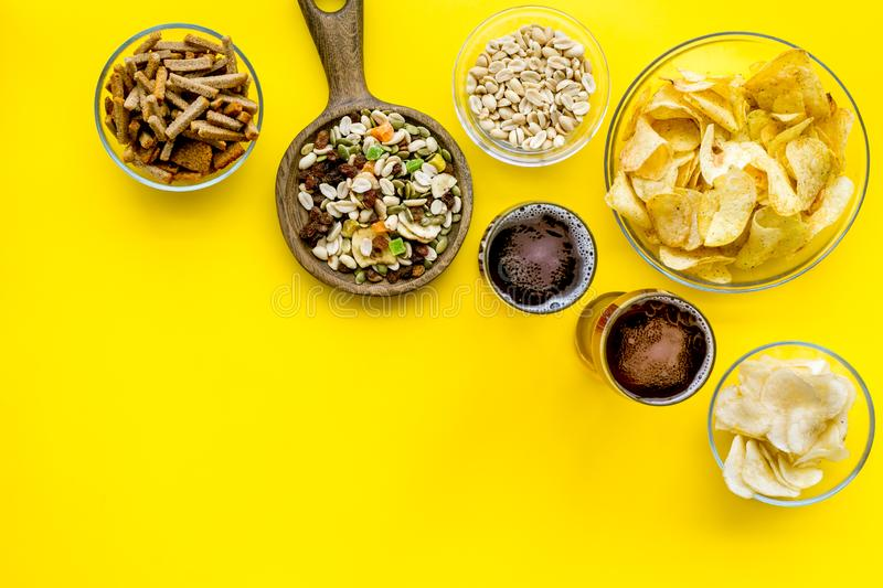 Fast food for TV watching. Snacks on desk. Chips, nuts, rusks and beer on yellow background top view space for text royalty free stock image