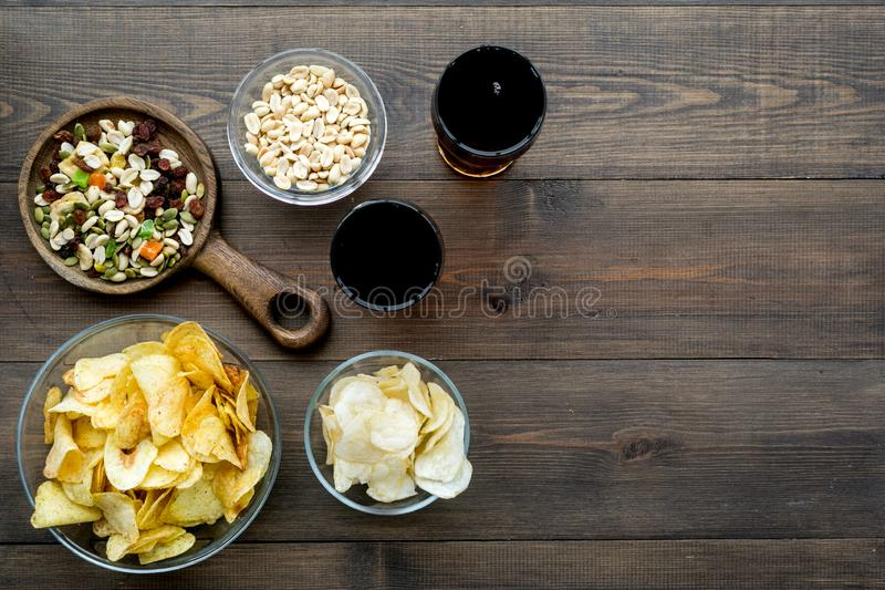 Fast food for TV watching. Snacks on desk. Chips, nuts, rusks and soda on dark wooden background top view copy space royalty free stock image