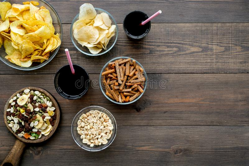 Fast food for TV watching. Snacks on desk. Chips, nuts, rusks and soda on dark wooden background top view copy space royalty free stock photo