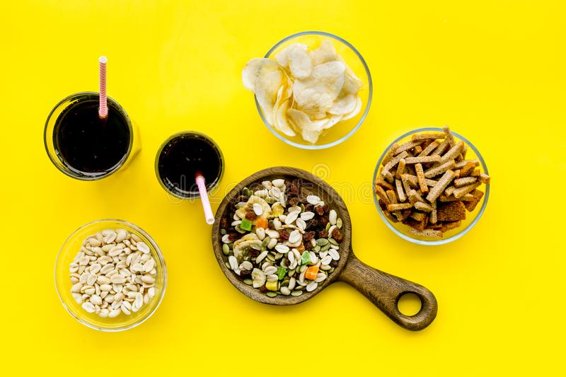 Fast food for TV watching. Snacks on desk. Chips, nuts, rusks and soda on yellow background top view stock photography