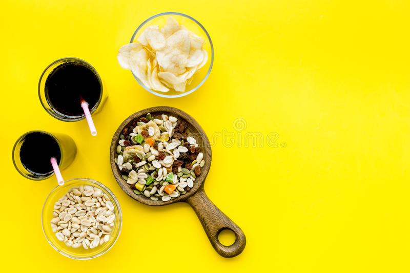 Fast food for TV watching. Snacks on desk. Chips, nuts, rusks and soda on yellow background top view copy space royalty free stock images