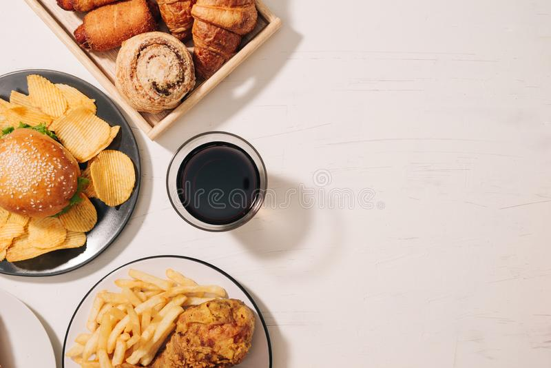 Fast food and unhealthy eating concept - close up of fast food snacks and cola drink on white table royalty free stock photo