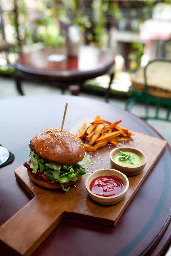 Fast food. Vegetarian burger with a chop, lettuce with sweet potatoes fries and two sauces. Tasty sandwich for lunch on wooden tab stock photo