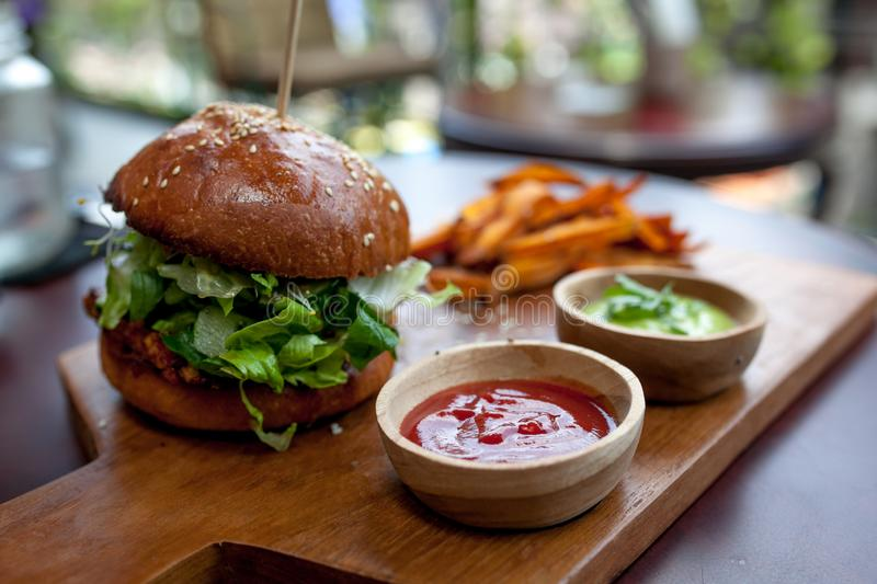 Fast food. Vegetarian burger with a chop, lettuce with sweet potatoes fries and two sauces. Tasty sandwich for lunch on wooden tab royalty free stock photography