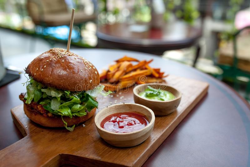 Fast food. Vegetarian burger with a chop, lettuce with sweet potatoes fries and two sauces. Tasty sandwich for lunch on wooden tab royalty free stock images