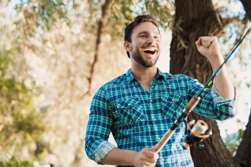 Fast gefangen Ein Mann in einem blauen Hemd steht auf der Flussbank mit einem Spinnen in seine Hände und dem Lächeln stockbilder