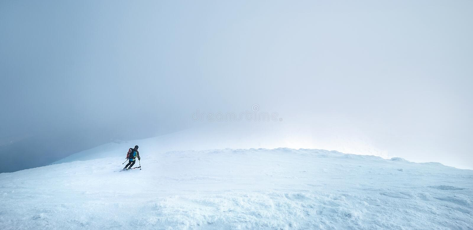 Fast going skier ride down the mountain hill into the storm clouds. Active winter sport concept image royalty free stock photography