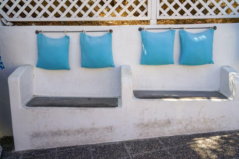 Fast inbyggd stol för plats för bänk för beställnings- design för vitbetong med ljus - blå kudde som hänger vid stålstången längs arkivfoton