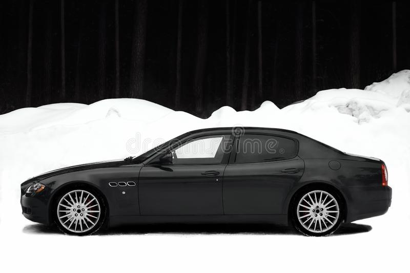 Fast Italian car in snowy Siberia on black and white background. GTS. Fast Italian car on a black and white background from a snowdrift and a dark forest royalty free stock image