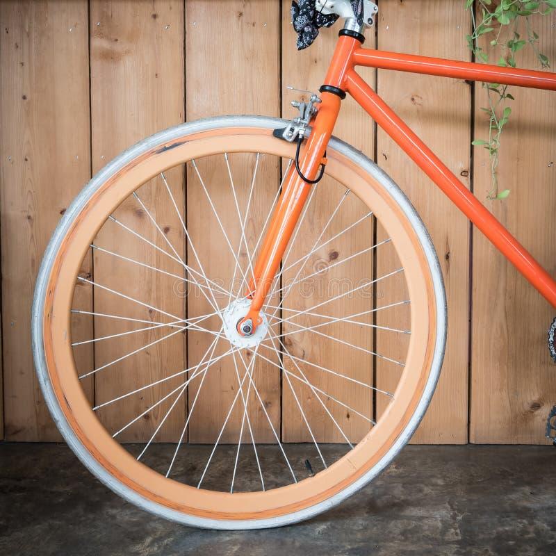 Fast kugghjulcykel som parkeras med den wood väggen, övre bild för slut arkivfoton