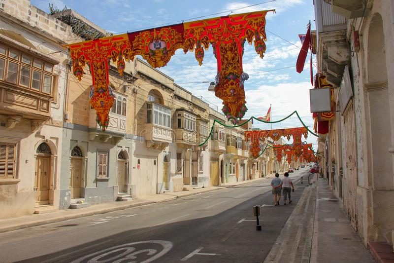 Fast leere festlich verzierte Straße mit alten traditionellen Balkonen Zwei Erwachsene, die unter Fahnen für jährliches festa rel lizenzfreie stockbilder