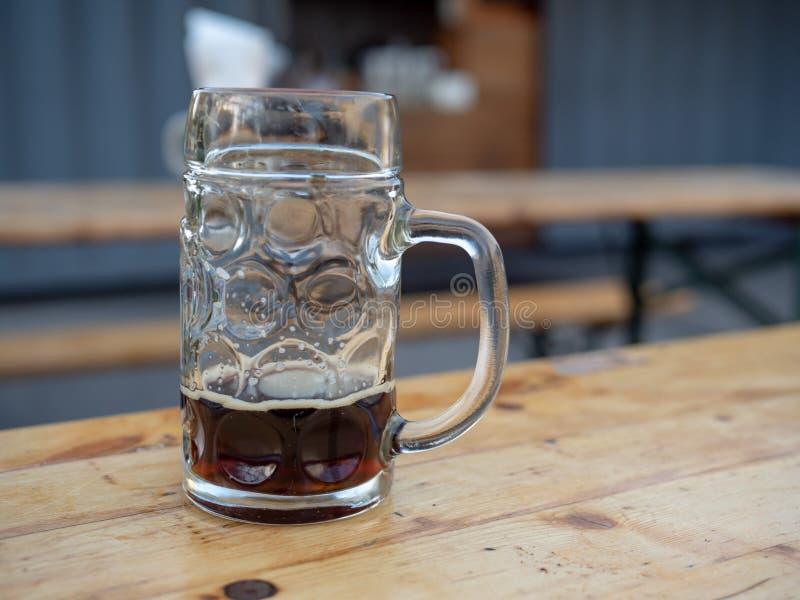 Fast leerer deutscher Bierkrug, der auf Tabelle sitzt stockfoto