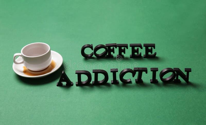 Fast leerer Tasse Kaffee mit Text KAFFEE-SUCHT auf Farbhintergrund lizenzfreies stockfoto