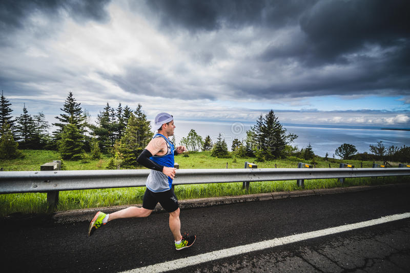 Fast Marathoner Alone going Down the Hill. CARLETON, CANADA - June 4, 2017. During the 5th Marathon of Carleton in Quebec, Canada. Fast Man Alone during the stock photos