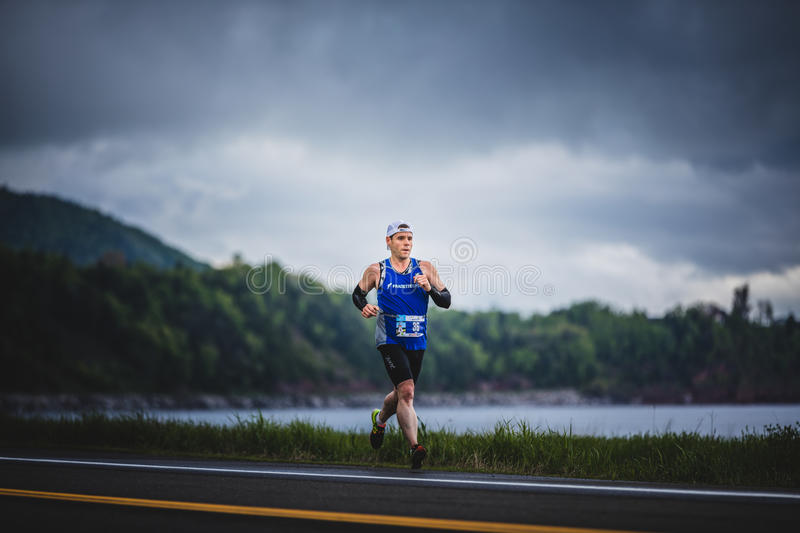 Fast Marathoner Alone going Down the Hill. CARLETON, CANADA - June 4, 2017. During the 5th Marathon of Carleton in Quebec, Canada. Fast Man Alone during the stock photography