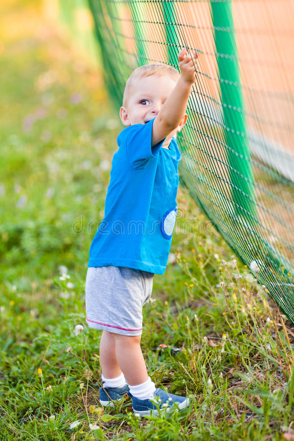 Fast! Until mommy doesn't see me!. Little boy playing, trying to climb up the fence royalty free stock image
