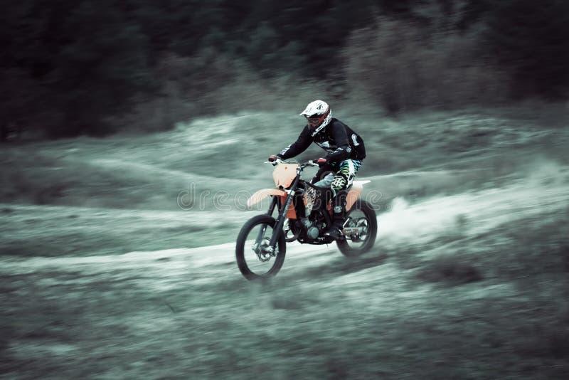 Fast motocross dirtbike rider on sand royalty free stock photos