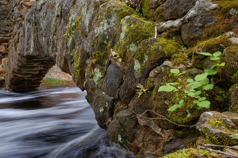 Fast moving stream flows under a historic stone arch royalty free stock images
