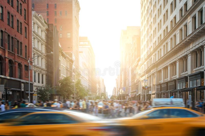 Fast-paced life in New York City street scene with cabs driving down 5th Avenue and crowds of people in New York City royalty free stock photo