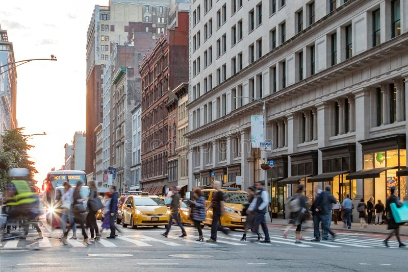 Fast paced street scene with people walking across intersection in New York City royalty free stock photography
