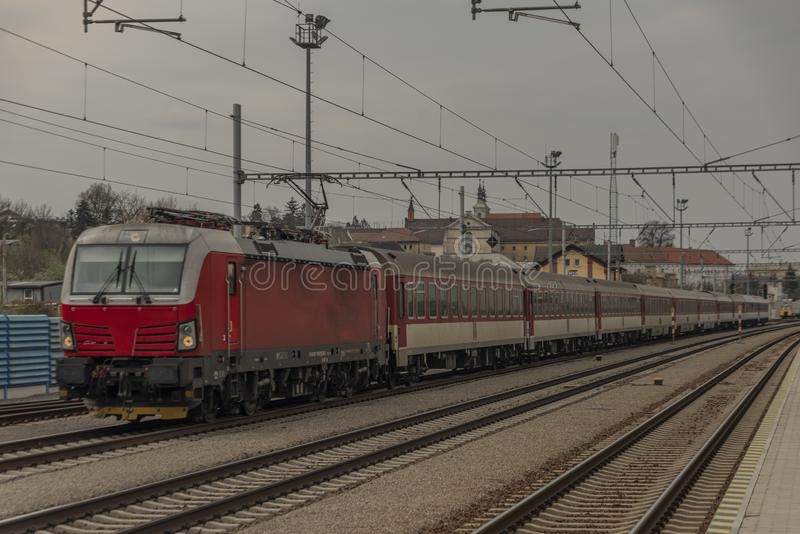 Fast passenger train with red modern electric engine in Ilava station. In west Slovakia, building, business, castle, cloudy, cold, dark, day, dusk, europe royalty free stock photography