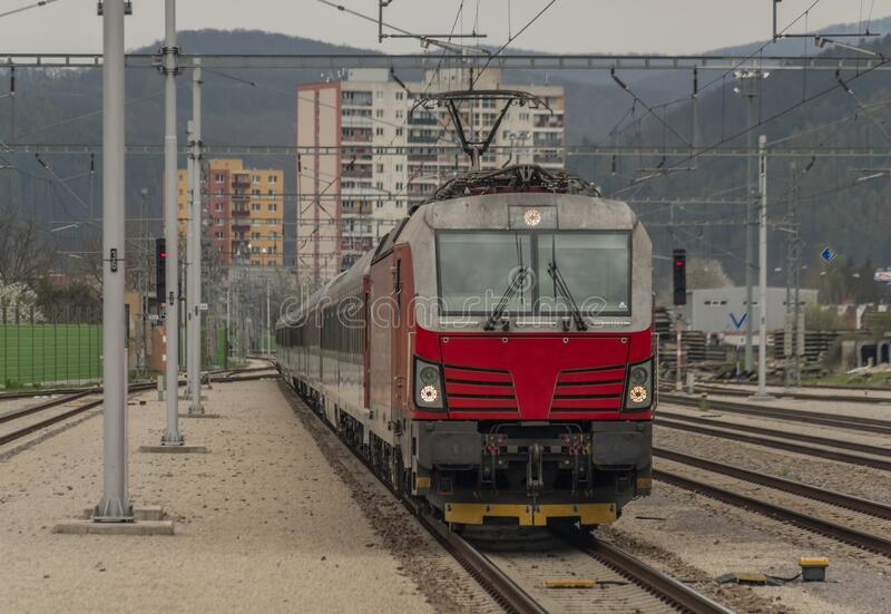 Fast passenger train with red modern electric engine in Trencin station. In west Slovakia, building, business, castle, cloudy, cold, dark, day, dusk, europe royalty free stock photos